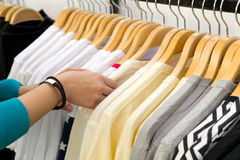 Young woman looking new shirt shopping in store. Young woman looking new shirt shopping in store Royalty Free Stock Photo
