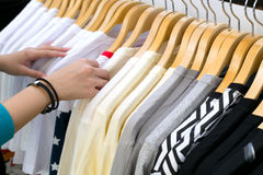 Young woman looking new shirt shopping in store. Young woman looking new shirt shopping in store Stock Image