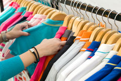 Young woman looking new shirt shopping in store. Young woman looking new shirt shopping in store Royalty Free Stock Images