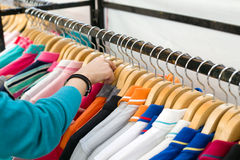 Young woman looking new shirt shopping in store. Young woman looking new shirt shopping in store Royalty Free Stock Photography