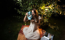 Young woman looking at old lantern while sitting at night garden Stock Photo