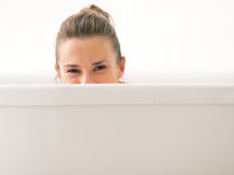 Young woman looking out from bathtub Stock Image