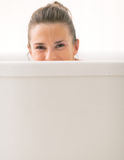 Young woman looking out from bathtub Stock Images
