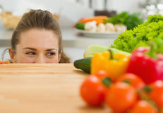 Young woman looking out from cutting board Royalty Free Stock Photography