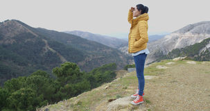 Young woman looking out over mountain scenery. With her hand to her forehead balancing on a rock as she enjoys the peaks and valleys Royalty Free Stock Photo