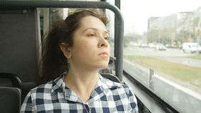 Young woman looking out the window of the bus. Big city stock footage