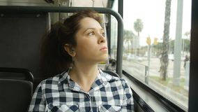 Young woman looking out the window of the bus. Big city stock video footage
