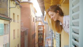 A young woman looking out of the window to a medieval street smiling and waving her hand. Nice, France. Apartments and villas for rent. Vacation Europe Travel stock footage