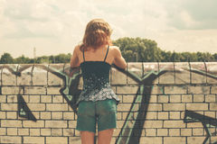 Young woman looking over wall Royalty Free Stock Image
