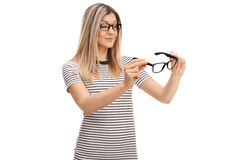 Young woman looking at a pair of glasses Stock Photography