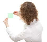 Young woman looking at paper note, rear view Stock Images