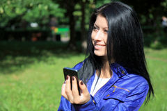 Young woman looking at phone and smiling Royalty Free Stock Image