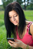Young woman looking at phone and smiling Royalty Free Stock Photography