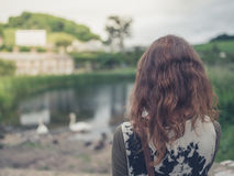 Young woman looking at pond Royalty Free Stock Images