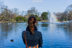 Young woman looking at pond Stock Image