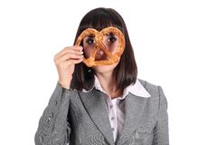 Young woman looking through pretzel Stock Image