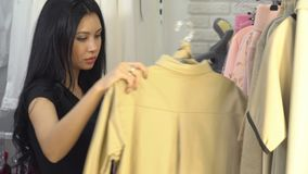 Young woman looking at a price label at a mall or clothing store.  stock footage