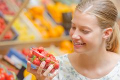 Young woman looking at punnet strawberries Royalty Free Stock Photo