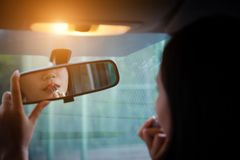 Young woman looking in rear view mirror and putting make up. Royalty Free Stock Photo