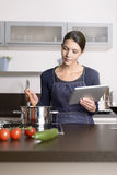 Young woman looking at a recipe on her tablet Royalty Free Stock Image