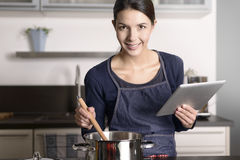 Young woman looking at a recipe on her tablet Royalty Free Stock Photo