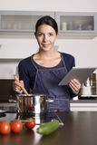 Young woman looking at a recipe on her tablet Royalty Free Stock Images