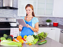 Young woman looking for a recipe online Stock Photography