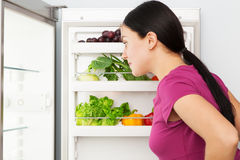 Young woman looking into a refrigerator Royalty Free Stock Photos