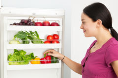 Young woman looking into a refrigerator Stock Images