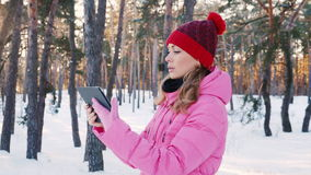 Young woman looking for the right way, using a tablet or a GPS navigator. M in the snowy winter forest stock video