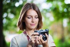 Young woman looking at screen of retro camera Royalty Free Stock Photo