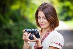 Young woman looking at screen of retro camera Royalty Free Stock Image