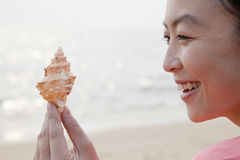 Young Woman Looking at Seashell Royalty Free Stock Photos