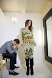 Young woman looking at self in mirror while man sitting on chair with hands on face Stock Images