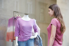 A young woman looking in a shop window Stock Images
