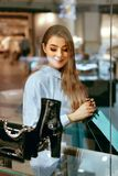 Young Woman Looking Through Shop Window. Young Beautiful Woman Looking Through Shop Window On New Clothes Or Shoes In Shopping Mall. High Resolution Stock Photography