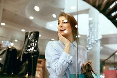 Young Woman Looking Through Shop Window. Young Beautiful Woman Looking Through Shop Window On New Clothes Or Shoes In Shopping Mall. High Resolution Stock Image