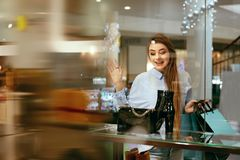 Young Woman Looking Through Shop Window. Young Beautiful Woman Looking Through Shop Window On New Clothes Or Shoes In Shopping Mall. High Resolution Stock Images