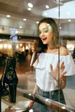 Young Woman Looking Through Shop Window. Young Beautiful Woman Looking Through Shop Window On New Clothes Or Shoes In Shopping Mall. High Resolution Royalty Free Stock Images