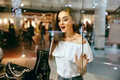 Young Woman Looking Through Shop Window. Young Beautiful Woman Looking Through Shop Window On New Clothes Or Shoes In Shopping Mall. High Resolution Stock Photo