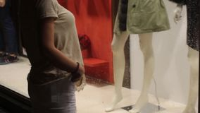 Young woman looking in shop windows stock video footage