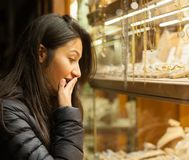 Young woman looking at the showcase of an outdoor jewelry Royalty Free Stock Photos
