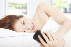 Young woman looking smart phone on the bed Stock Images