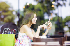 young woman looking at smart phone in cafe shop Stock Images