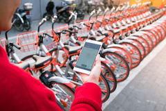 A young woman  is looking at smart phone to find her bicycle Royalty Free Stock Image