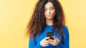 Woman smartphone doubt skepticism suspicious wary. Young woman looking at smartphone. Pursed lips. Skepticism doubt facial expression. Suspicious incredulous stock photography