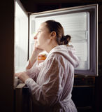 Young woman looking for some snack in fridge late at night Stock Image