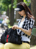 Young woman looking for something in your handbag Royalty Free Stock Photo