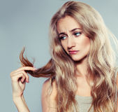 Young woman looking at split ends Royalty Free Stock Photos