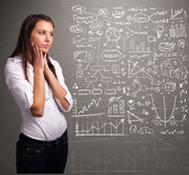 young woman looking at stock market graphs and symbols Stock Images
